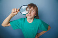 European looking boy of ten years a joke looking through magnifying glass keen eye on gray background Stock Images