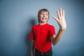 European looking boy of ten years shows four fingures a figure fingers on a gray background Royalty Free Stock Photo