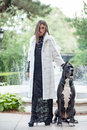 European model in a white fur coat and black dress posing outdoo Royalty Free Stock Photo