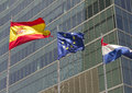 European spanish and french flag with modern building on the background Royalty Free Stock Photo
