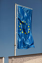 European union flag hoist on a metal flagpole against a blue sky Stock Photos