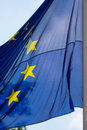 European union flag waves in cloudy sky eu bright sun against a blue Royalty Free Stock Photo
