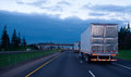 Evening convoy semi trucks trailers on straight interstate highw the of with reefer flat like an arrow road with lights and Royalty Free Stock Image