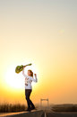 In the evening girl with a guitar on the road time colorful sky background she was very happy Stock Images
