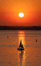 Evening sailing vessel silhouette in the sea at sunset Stock Photos