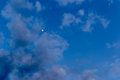 Evening sky cloudy with moon peeks Royalty Free Stock Photography