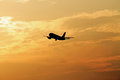 In the evening sky starting airplane into orange clouds Royalty Free Stock Image