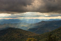 Evening sun rays over blue ridge mountains north carolina as the sets east fork overlook off the parkway from textured clouds Stock Photos