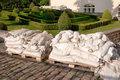 Evening sunlight on sandbags prepared for flood prevention around topiary in sunshine Stock Photos
