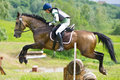 Eventer on horse is overcomes the cross-country fence Stock Photo