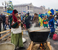 Everyday life on the maidan in kiev ukraine december elderly man national dress cossack prepares food a large cauldron to people Stock Image