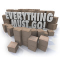 Everything must go boxes overstock inventory store closing sale words in d letters surrounded by cardboard in a warehouse to Royalty Free Stock Photos