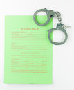 Evidence form and hancuffs aerial view of a green unfilled with the title a pair of handcuffs with keys against a white background Royalty Free Stock Image