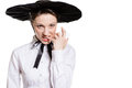 Evil angry pretty woman with mobile phone looking on copyspace over white background young surprised in huge black hat closeup Stock Photos