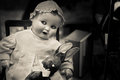 Evil baby doll staring with bunny rag Royalty Free Stock Photos
