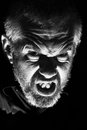 Evil man low key head shot of with extreme rage and anger with a sneer Stock Images
