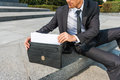 This is exactly what i need close up of confident young man in formalwear taking the documents from briefcase while sitting Stock Image