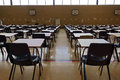 Exam tables are set out in a sports hall ready for exams Stock Image