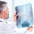 Examining x ray rear view of confident mature grey hair doctor image while standing isolated on white Stock Photo