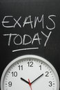 Exams today and wall clock written in white chalk on a blackboard above a Royalty Free Stock Photos