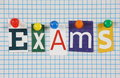 Exams the word in cut out magazine letters pinned to a background of blue graph paper Royalty Free Stock Photography
