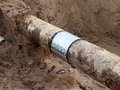 Excavation pit. Old drink water pipe with stainless repairing sleeve members. Royalty Free Stock Photo