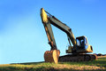 Excavator on blue sky. Royalty Free Stock Photography