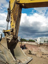 Excavator closeup of a shovel new apartments in the background Royalty Free Stock Photography