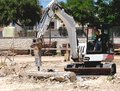 Excavator with hammer demolishes Stock Photography