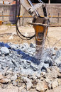 Excavator with hydraulic hammer breaking concrete on a construction site Stock Photography