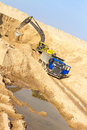 Excavator loading dumper truck at construction site Royalty Free Stock Photo