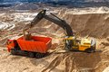 Excavator loading dumper truck at construction site Stock Images