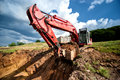 Excavator loading dumper truck tipper in sandpit highway construction site and quarry Royalty Free Stock Photography