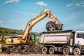 excavator loading dumper trucks at garbage dumping site Royalty Free Stock Photo