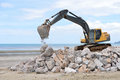 Excavator machine moves with raised bucket during stone moving works Stock Photos