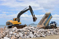 Excavator machine moves with raised bucket during stone moving works Stock Photography