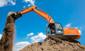 Excavator with metal tracks unloading soil at construction site Royalty Free Stock Photo