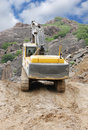 An excavator moving on top level of a granite mine Stock Photography