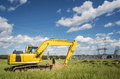 Excavator in a power plan on a summer day with blue sky and clouds Royalty Free Stock Photos