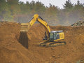 Excavator power shovel digging in a gravel pit Stock Images