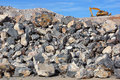 Excavator on rock pile works demolishing a path through a mountain Royalty Free Stock Image