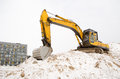 Excavator sand pit snow winter apartment house stand on quarry pile soil covered with and new modern in construction industry Royalty Free Stock Photography