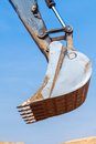 Excavator scoop bucket across the blue sky Stock Image