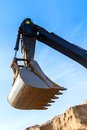 Excavator scoop bucket across the blue sky Stock Photos