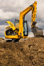 Excavator standing on soil with open engine Stock Photos
