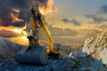 Excavator in stone quarry image of a tracked a with a setting sun and light rays Royalty Free Stock Photography