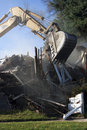 Excavator tearing apart a house Stock Photo