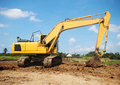 Excavator working at construction site yellow Royalty Free Stock Image