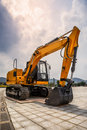 Excavator a yellow parked in open space Royalty Free Stock Image