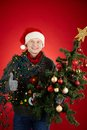 Excellent holiday portrait of happy man in santa cap decorated xmas tree showing thumb up Stock Photo